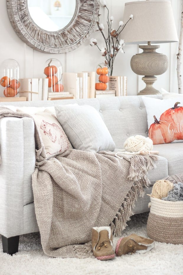 Cozy living room decor with pillows and throws. Loving the nude and pumpkin tones.