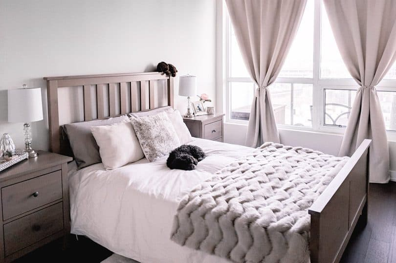 A cozy bedroom makeover with fresh linens, a fur throw, and textured pillows.
