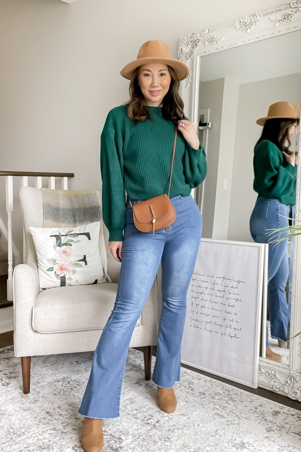 Cute fall outfit ideas - flared jeans are back! This casual outfit with flared jeans, green sweater, brown boots, hat and saddle bag is perfect for everyday, running errands, or going to school!