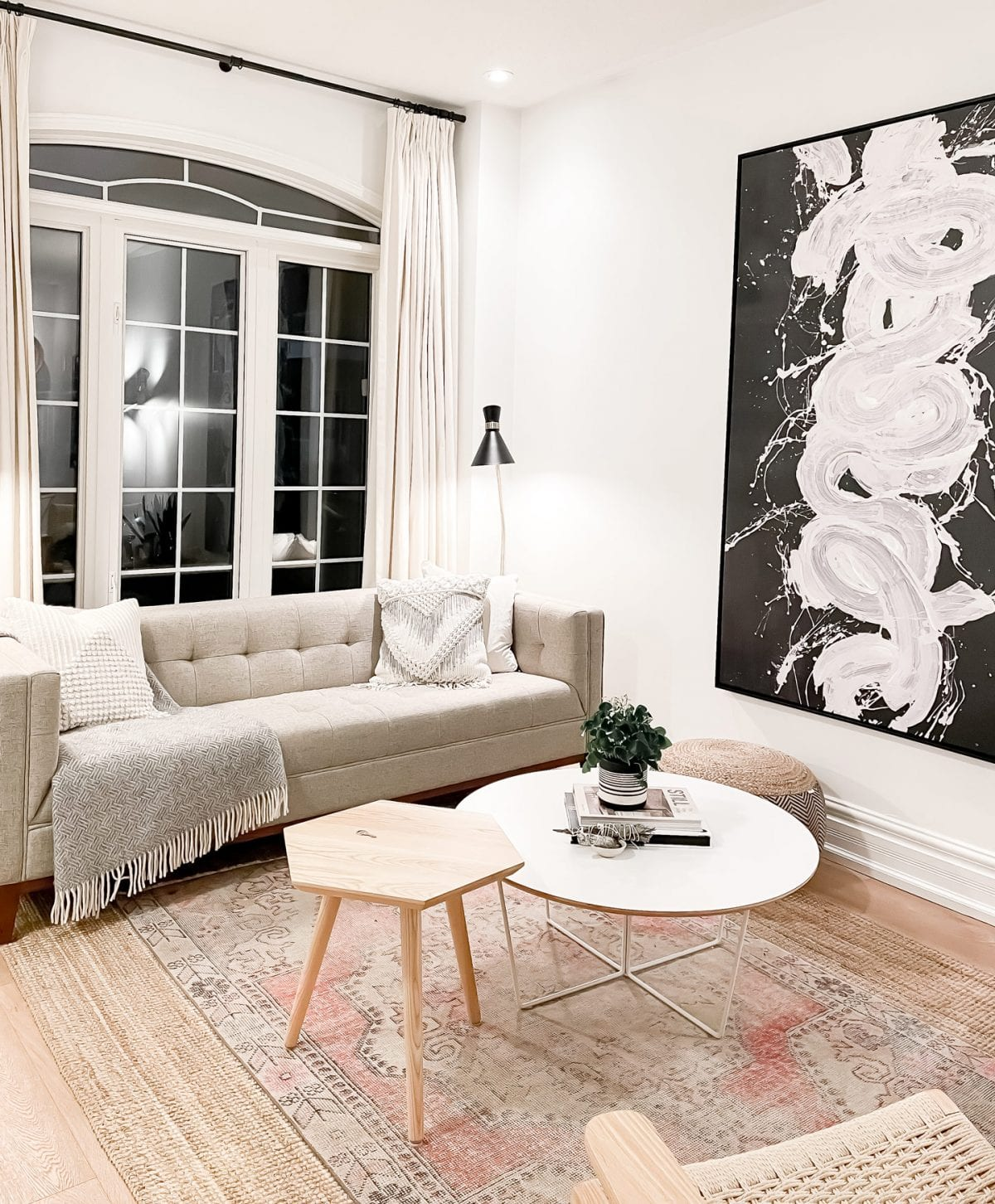 5 valuable tips for home buying. This is a beautiful living room with a modern mid-century sofa, contemporary artwork and scandinavian furnishings.