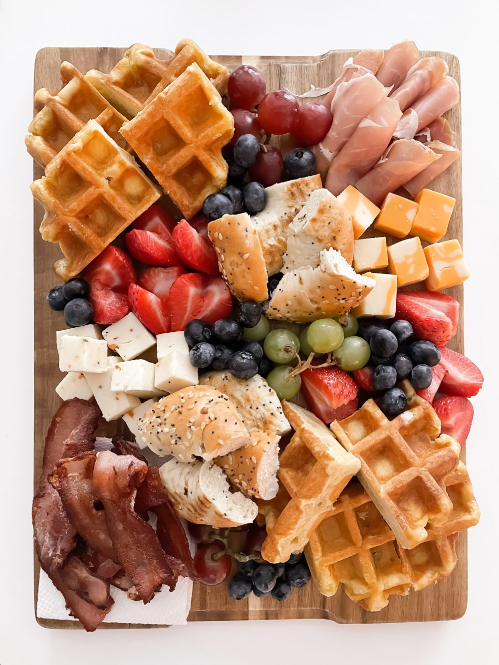 Easy breakfast idea - brunch board with waffles, strawberries, bagels, bacon, proscuitto, cheeses and more!