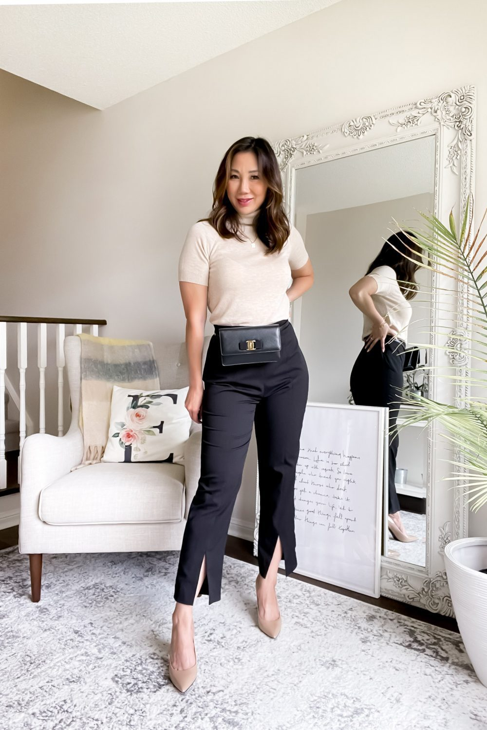 Chic office outfit with knit sweater and black pants with waist bag.